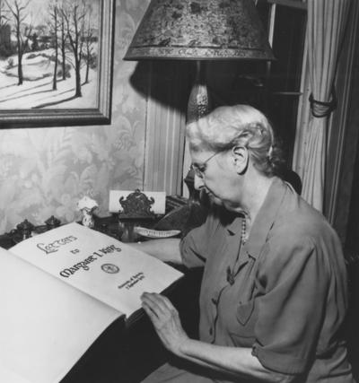 King, Margaret I., looking at a book titled Letters to Margaret I. King, She is the University of Kentucky's first librarian, she began her career as President Patterson's Secretary, The current Margaret I. King Library, formerly the Central Library, which opened in 1931, was named for her when she retired in 1948