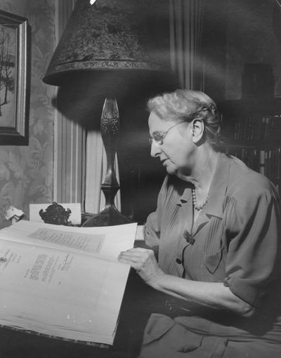 King, Margaret I., looking at a book titled Letters to Margaret I. King, She is the University of Kentucky's first librarian, she began her career as President Patterson's Secretary, The current Margaret I. King Library, formerly the Central Library, which opened in 1931, was named for her when she retired in 1948, Photograph received from Mrs. Frances Shine on November 2, 1966