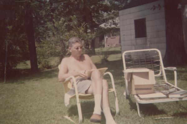 Kirwan, Albert, University of Kentucky President from 1968-1969, sitting on a sunny lawn reading