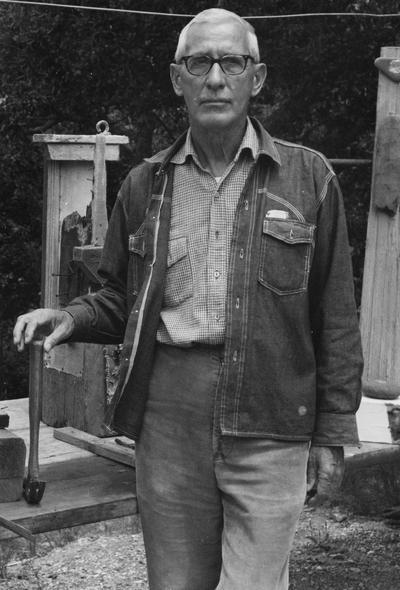 Barnhart, Raymond C., Professor, Department of Art, standing outdoors with his sculptures, photographer: Gen Barnhart