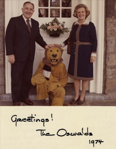 Oswald, John W., President at the University of Kentucky 1963-1968, Dr. and Rosanel Oswald pictured with Nittany Lion Mascot at doorway of their home as President of Penn State University (1970 - 1983): University Park Campus (State College, Pennsylvania)