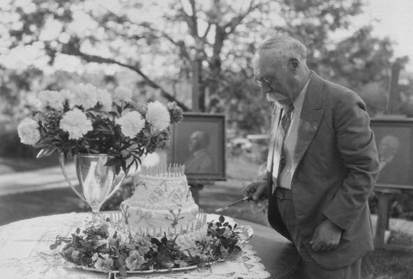 Peter, Alfred Meredith, birth 1857, death 1953, Chemist-Experiment Station 1880-1934, Emeritus Professor of Soil Technology, pictured at his retirement party about to cut the cake, the portraits of Dr. Peter and his father are in the background