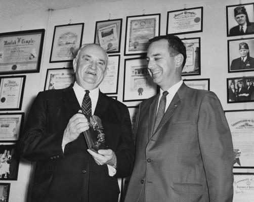 Rupp, Adolph, University of Kentucky Basketball Coach 1930-1971, pictured receiving award, from Public Relations Department