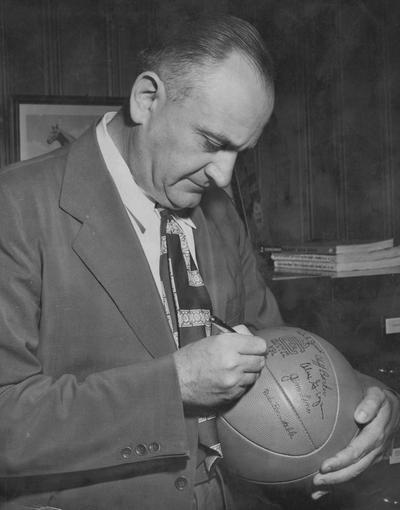 Rupp, Adolph, University of Kentucky Basketball Coach 1930-1971, pictured autographing basketball, Lexington Herald Leader Staff Photo