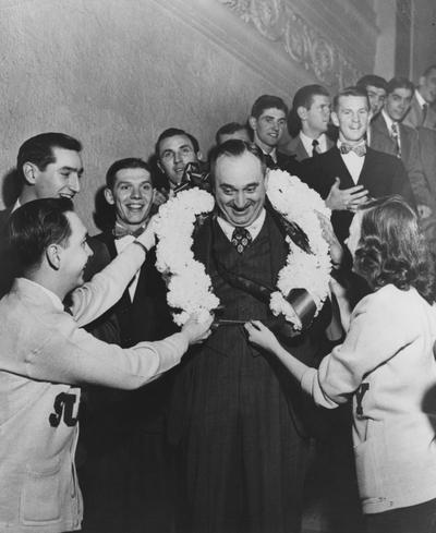 Rupp, Adolph, University of Kentucky Basketball Coach 1930-1971, pictured recieving a wreath after NCAA championship in 1949, also pictured are Alex Groza, Ralph Beard, Cliff Barker, Roger Day, Jim Line, Dale Barnstable, Al Bruno, Walt Hirsch, Chapter 24