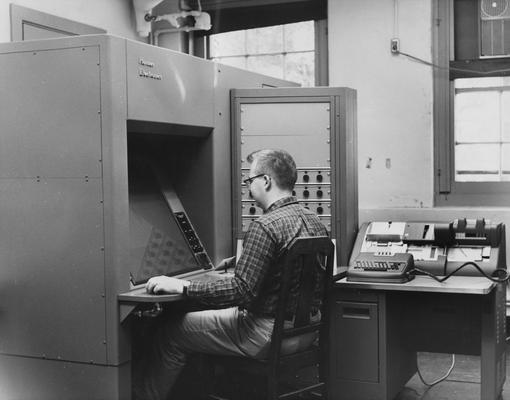 Vittitoe, Charles N., graduate student in physics at the University of Kentucky, pictured wroking on a new electronic measuring device in calculating actions of subatomic particles previously photographed by another device, the machine is only the second of its kind