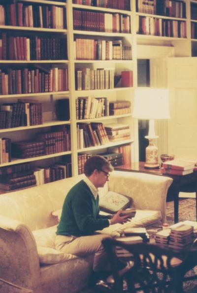 Willis, Paul A., Director of Library Department, pictured sitting on couch looking through stacks of books in the library shelving