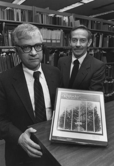 Willis, Paul A., Director of Library Department, pictured standing in library shelving with Rex Boggs