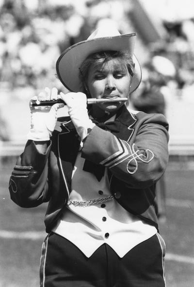 Unidentified, woman University of Kentucky band member playing the piccolo instrument in the marching band, Photographer: Ken Goad,