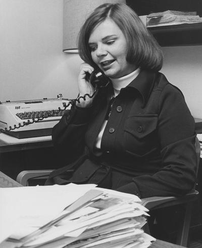 Unidentified woman sits at a desk and talks on a phone in the Medical Center