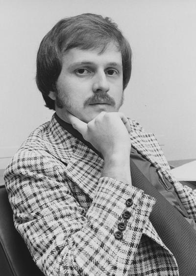 Unidentified male Medical Center employee sits at a desk