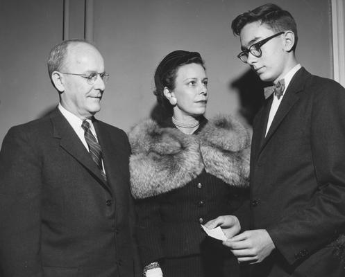 Chamberlain, Leo M., Professor, Education, University Vice President, Receiving a donation on behalf of the University from Mrs. Jack Webb, Sr. and Jack Webb, Jr., to start a loan fund for students and the College of Medicine, Public Relations Department photograph, featured in April 7, 1958 Louisville Courier - Journal