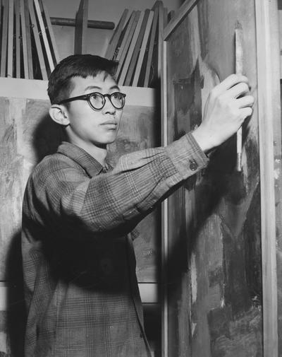 Chou, Ju - Hsi, Alumnus,, Art, pictured working on a painting, Public Relations Department, Featured in Louisville Courier - Journal, January 31, 1958