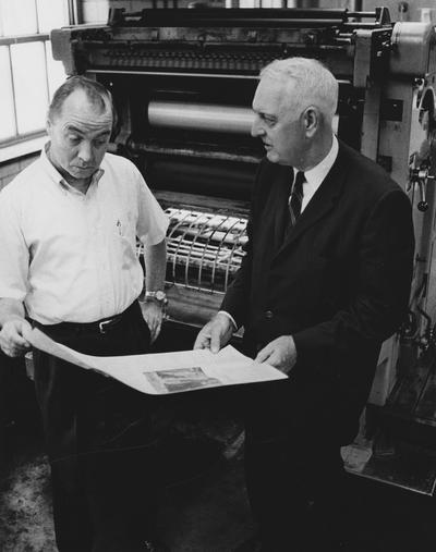 Clark, Thomas D., Alumnus, Master of Arts, 1929, Distinguished Professor, History Department, 1931 - 1968, Noted author and historian, Expert on Kentucky and Southern culture, pictured with unidentified man looking at  copy from printing press, Public Relations Department photograph