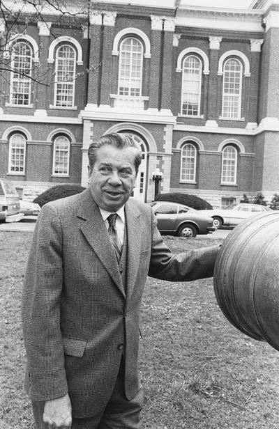 Cochran, Lewis W., Professor, Chemistry Department, Vice President for Academic Affairs, pictured with cannon in front of Administration Building