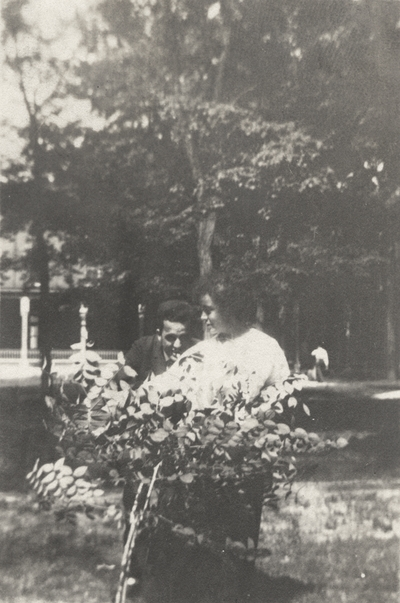 An image of Margaret Ingels and a man (possibly her older brother) standing behind a small bush