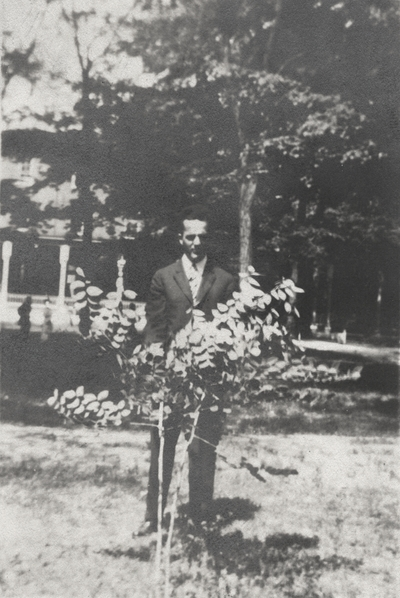 An image of a man (possibly her older brother) standing behind a small bush. This image was found pasted on the front of page 100 of