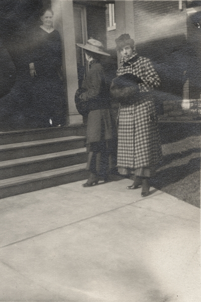 An image of a woman posing in front of a building and a man and woman talking on the left side of the print. This image was found pasted on the front of page 100 of
