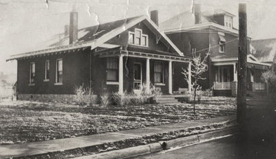 An image of a one and a half story house (same house as in image 16) in the foreground and a two and a half story house in the background. This image was found pasted on the back of page 100 of