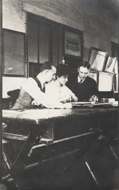 A postcard of Margaret Ingels and two men sitting at a drafting table. This image was found pasted on the front of page 103 of