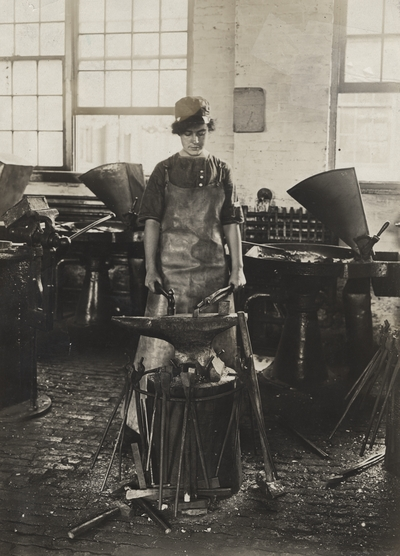 A portrait of Margaret Ingels standing behind a forge preparing to work on metal. This image was found pasted on the front of page 102 of