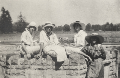 A portrait of four unidentified women sitting and leaning on a stone wall. This image was found pasted on the front of page 100 of