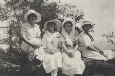 A portrait of four unidentified women sitting on a log. Margaret Ingels may by the woman on the far left with her arms around her knees. This image was found pasted on the front of page 100 of