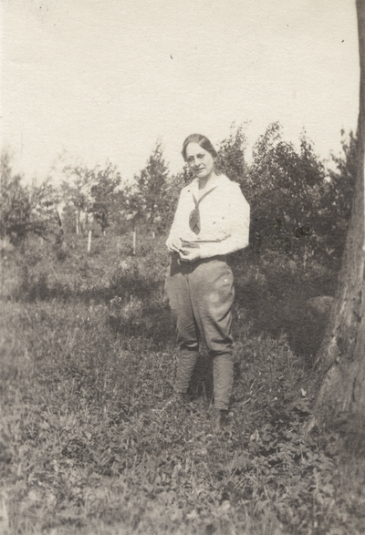 A portrait of a woman standing in a field. This image was found pasted on the front of page 108 of