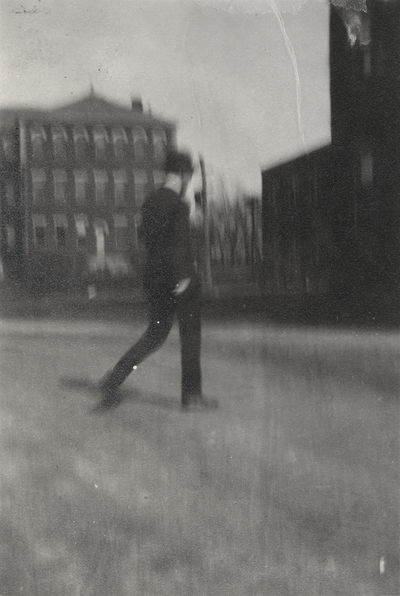 A blurred image of a man walking on the University of Kentucky campus. This image was found pasted on the front of page 103 of