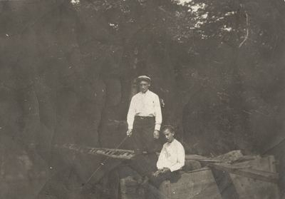 An image of Charles Christopher Schrader as a teenager with another boy fishing. There is a note on the back from Charles Christopher Schrader