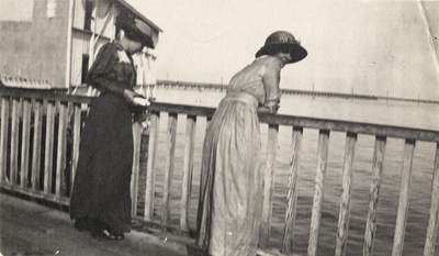 An image of two women looking over a pier. This image was found in the