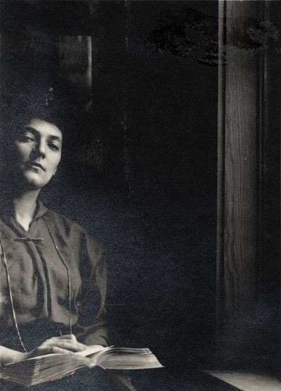 A portrait of an unidentified woman sitting with a book open on her lap and next to a window. This image was found pasted to the front of page 101 of the