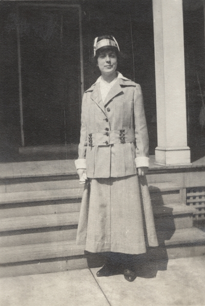 A portrait of Margaret Ingels standing in front of the steps of a house. This print was found pasted to the front of page 102 of
