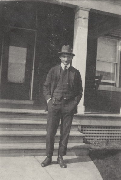 A portrait of Charles Christopher Schrader standing in front of the steps of a house. This print was found pasted to the back of page 102 of