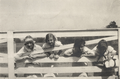 An image of four young ladies with their heads through a fence. Margaret Ingels is the second girl from the right. This image was found pasted on the front of page 100 of