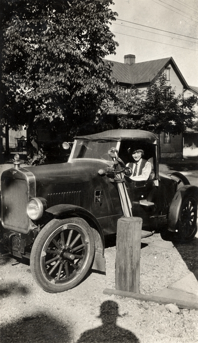 A portrait of Helen Cochran sitting in of a Ford Model A, which they called