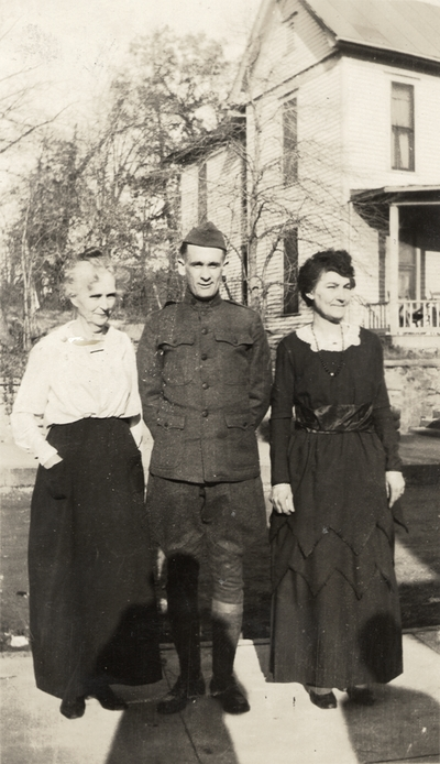 A portrait of two unidentified women and a man in a military uniform standing on a sidewalk (the woman on the far left is possibly Margaret Ingels' mother). Taken by De Lure Studio, Hot Springs, Arkansas. This print was found pasted to the back of page 108 of