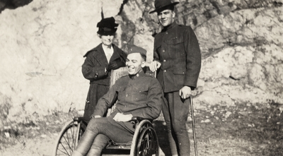 A portrait taken outside of two unidentified men in military uniforms and an unidentified woman (the woman may be Margaret Ingels' mother). One of the men has a cane and the other is sitting in a wheel chair. Taken by De Lure Studio, Hot Springs, Arkansas. This print was found pasted to the back of page 108 of
