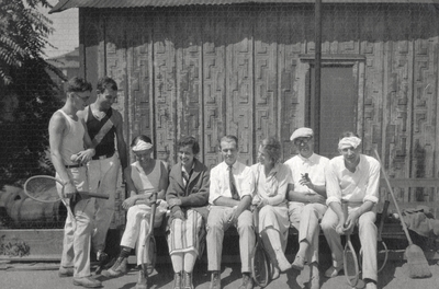 A group portrait of eight persons in tennis playing clothes and tennis rackets. Margaret Ingels is wearing a stripped skirt