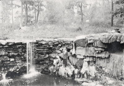 A image of a group of five women next to a waterfall. Margaret Ingels may be the woman all in white wearing a hat. This print was found pasted to the front of page 104 of