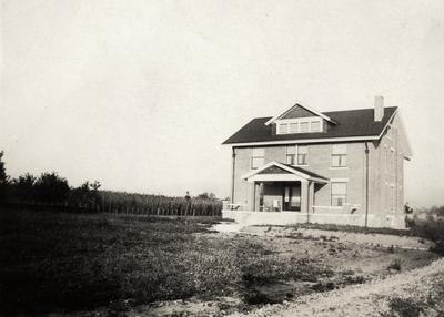 An image of a two and a half story brick house with a corn field on the left. This print was found pasted to the back of page 105 of