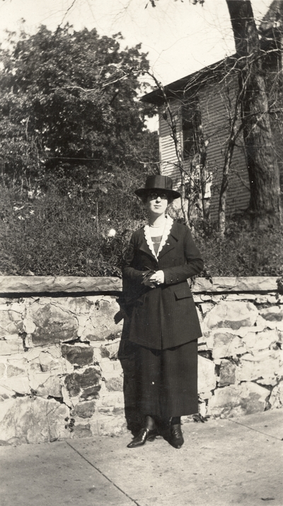 A portrait of an unidentified woman standing on a sidewalk next to a stone wall. This print was taken by De Luxe Studio, Hot Springs, Arkansas. This print was found pasted to the front of page 109 of