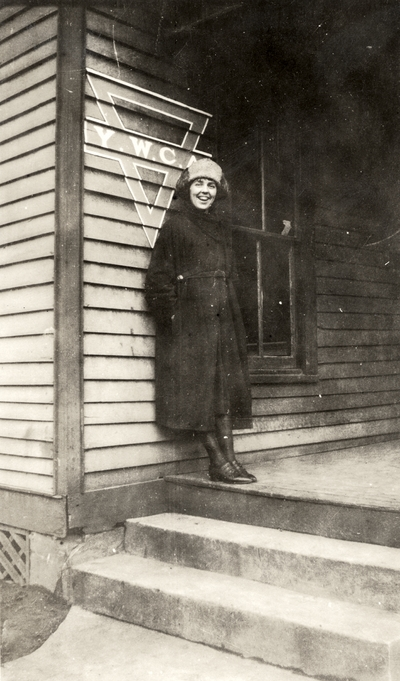 A portrait of an unidentified woman standing on the steps of a Y. M. C. A. (Young Women's Christian Association) residence. This print was found pasted to the back of page 115 of