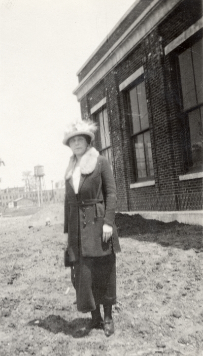 A portrait of an unidentified woman standing in dirt next to a building. This print was found pasted to the front of page 112 of