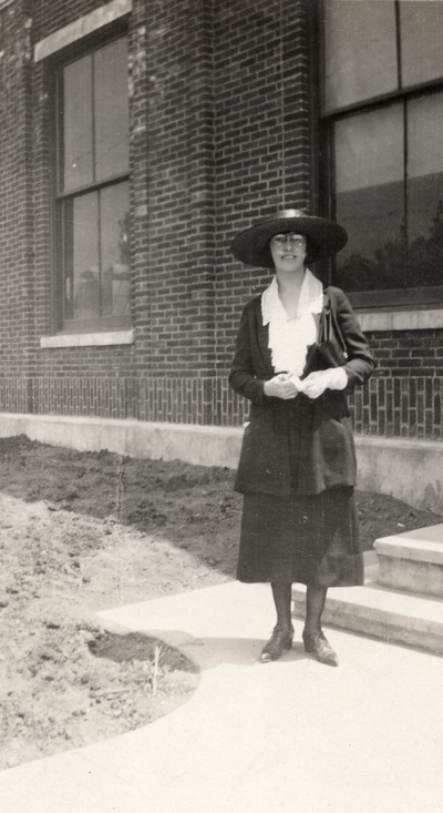 A portrait of an unidentified woman standing on a sidewalk next to a building. This print was found pasted to the front of page 112 of