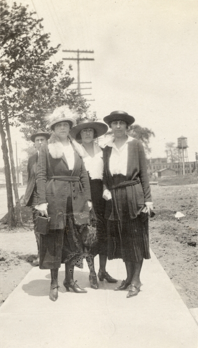 A portrait of three unidentified women and a man standing on a sidewalk (the woman on the far right may by Eva Allen). This print was found pasted to the front of page 112 of