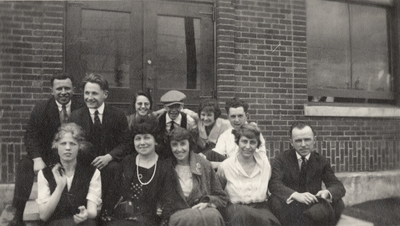A group portrait of men and women on the steps of a building. This print was found pasted to the front of page 112 of