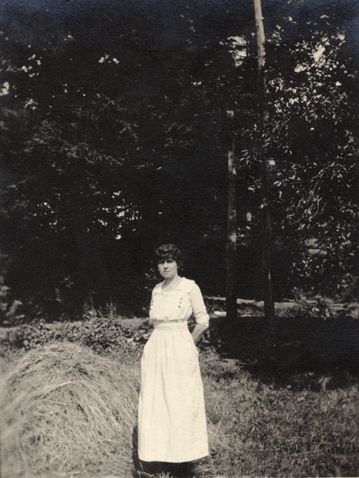 A portrait of a woman standing in a field next to a haystack and some trees. This print was found pasted to the back of page 110 of
