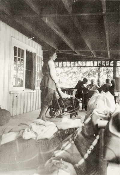An image of group of unidentified persons sitting and standing on a porch. The back of the print is stamped