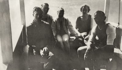 A group portrait of men and women sitting together. Some of the persons are wearing bathing suits. This print was found pasted to the back of page 116 of